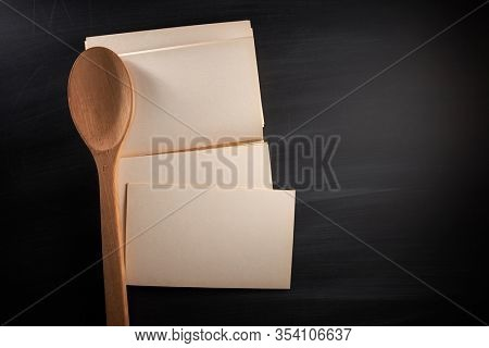 Blank, empty, black chalkboard with wooden cooking spoon and old recipe book flat lay from above on blackboard