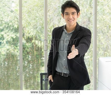 A 25-35 Year Old Asian Business Man In A Black Suit Smiled Happily And Extended His Hand In Front To