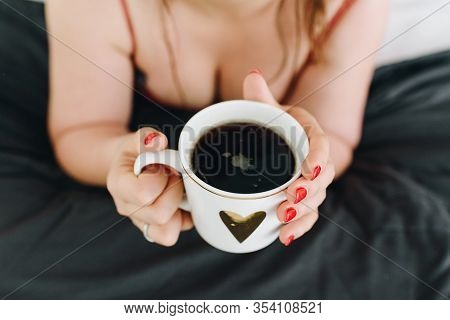 Cleavage Or Female Breasts, Young Woman Drinking A Cup Of Coffee  In Her Bed