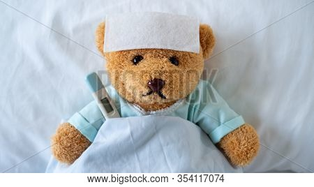 The Teddy Bear Is Sick On The Bed With A High Fever. There Is A Fever Reducing Sheet On The Forehead