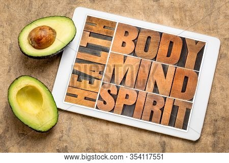 health, body, mind and spirit word abstract in vintage wood letterpress wood type on a digital tablet with avocado, holistic aproach to wellbeing concept