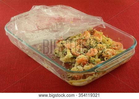 Leftovers Of Shrimp, Pasta, Tomato And Asparagus Casserole In Glass Baking Pan With Plastic Wrap Cov