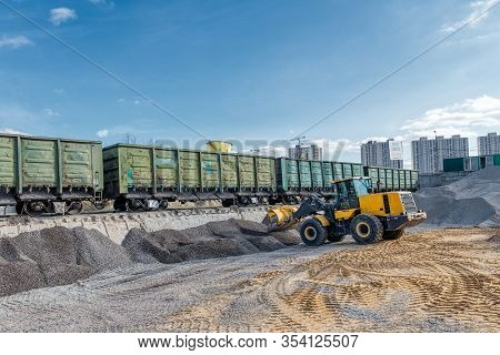 Wheel Loader Picks Gravel In The Bucket. Work On A Flyover For Unloading Railway Freight Cars. Trans