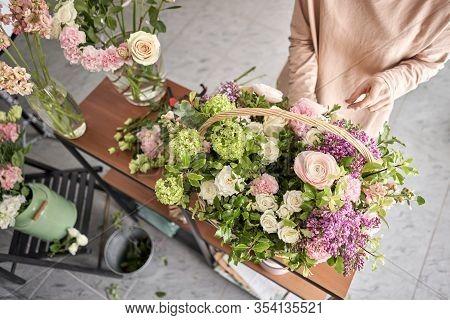 Floral Shop Concept . Florist Woman Creates Flower Arrangement In A Wicker Basket. Beautiful Bouquet