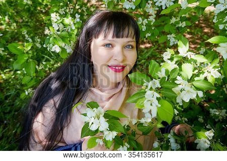 Portrait Of An Fat Chubby Plump Girl With Black Hair And Blossoming Apple Tree With White Flower Bac