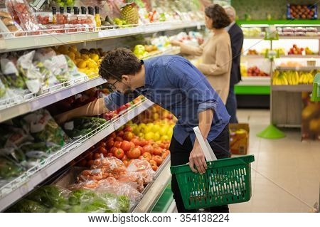 Focused People Shopping In Grocery Store. Side View Of Men And Woman Holding Shopping Baskets And Ch