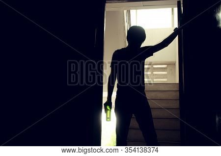 The Silhouette Of Young Men Standing And Holding A Bottle Of Alcohol Or Beer At The Old Condo, Unhea
