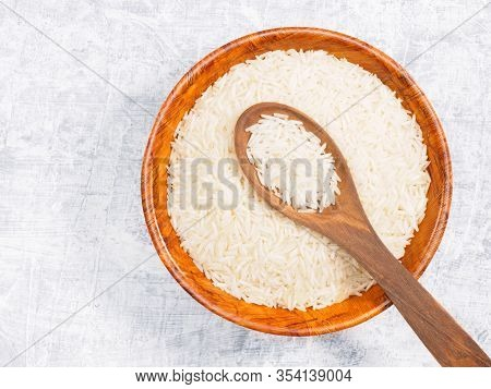 Indian Long Grain Basmati Rice In Brown Wooden Bowl And Spoon On White Concrete Background. Indian C