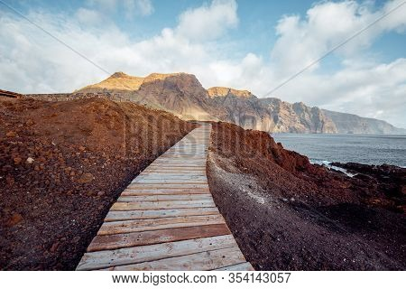 Landscape With Picturesque Wooden Pathway Through The Rocky Land And Mountains On The Background. No