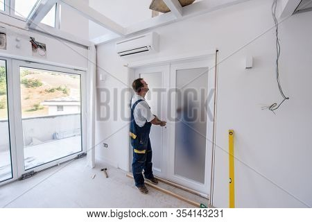 male workers carpenters installing interior glass door with a wooden frame at new luxury apartment