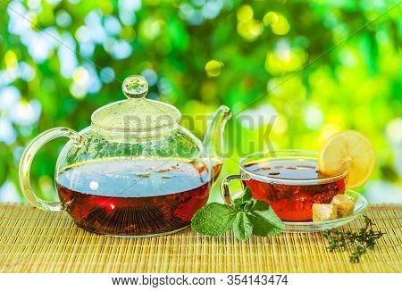 Tea ceremony. Glass teapot with brewed tea is on the table on a sunny summer day. In the background bokeh of beautiful nature.