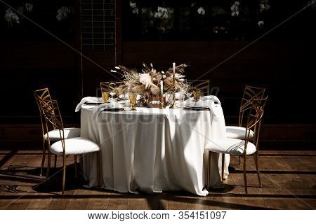Elegant Banquet Decor In Warm Autumn Colors. Tables With White Tablecloths Decorated With Bouquets O