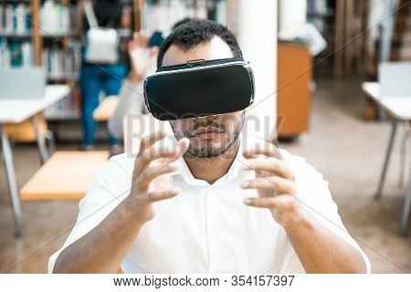 Excited Male Student Using Vr Simulator During Class. Latin Man In Virtual Reality Glasses, Sitting