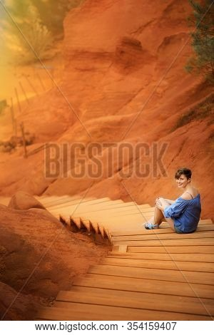 Vertical Picture With Young Woman Tourist On Vacation Sitting On Path In Ochre Quarry In One Of The