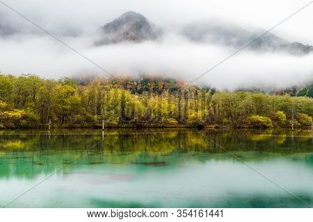 Lake Taisho In Kamikochi National Park With Misty In Morning Time, Water Reflection. The Lake Is Loc