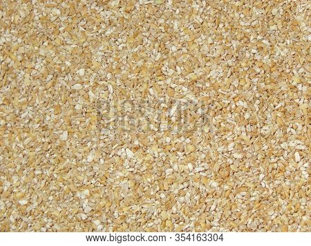 Background Of Ground Wheat Grits. Background Texture Of Porridge Made From Crushed Wheat. Dietary An
