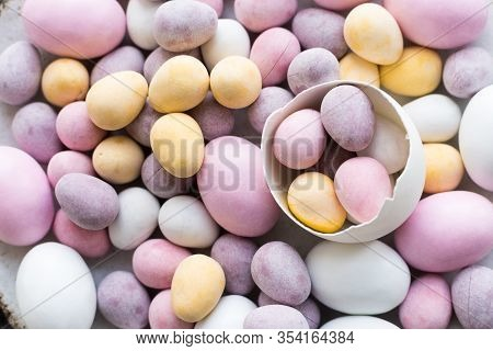 Easter Composition With Mini Chocolate Eggs In Pastel Colors On Grey Concrete Background. Happy East