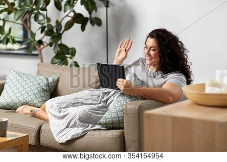 technology, leisure and people concept - happy smiling woman with tablet pc computer having video chat and waving hand at home