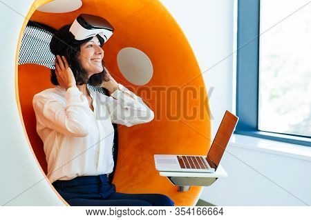 Happy Businesswoman With Vr Headset And Laptop Impressed With Simulator. Woman In Office Clothes And