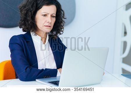 Confused Frowning Businesswoman Getting Concerning News. Business Woman Sitting At White Conference
