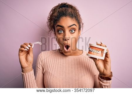 Young african american woman surprised and shocked holding professional orthodontic denture with metal braces and removable invisible aligner. Comparation of two dental straighten treatments
