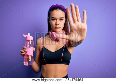 Beautiful sporty girl doing sport using headphones drinking bottle of water to refreshment with open hand doing stop sign with serious and confident expression, defense gesture
