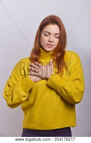 Calm Young Woman With Hands On Chest. Tranquil Young Woman Standing With Closed Eyes And Holding Han