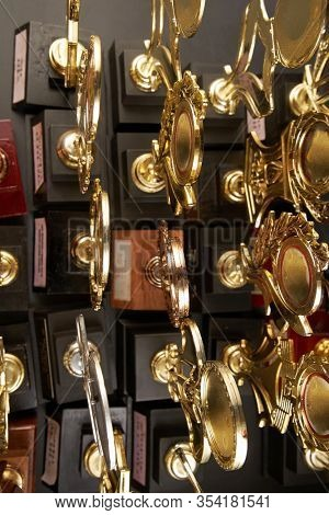 Group of golden trophy over blackboard background. top view. flat lay.Trophy is a specific achievement, serves as recognition / evidence of merit, awarded for sporting events