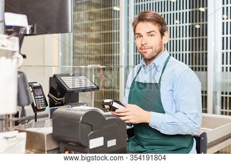 Man as a cashier with green apron at the cash register in the supermarket