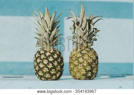 Closeup Of Two Fresh Pineapples Standing On Table Against Bright Blue Wooden Background. Ripe Delici