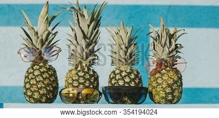 Closeup Of Funny Fresh Exotic Fruits Ananas On Table Against Bright Blue Wooden Background. Fashiona