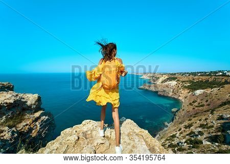 Rear View Of Traveler Woman Standing On Top Rock Beach With Backpack, Bright Yellow Dress And Hair B
