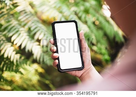 Mockup Image Of A Person Holding White Blank Screen Smart Phone With Blur Green Nature Background. M