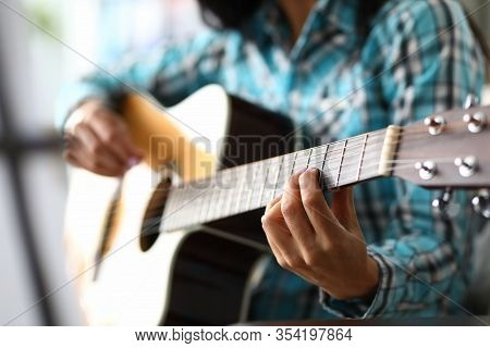 Skillful Musician Fingers On Guitar Fretboard. Woman Plays Chords On Acoustic Guitar, In Her Other H