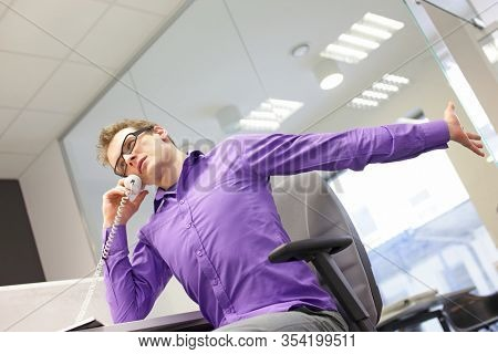 sitting caucasian man office worker with phone in hand, stretching arm and neck , exercising during work  in his office