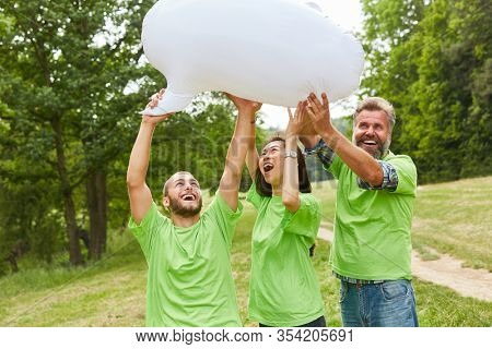 Three young people as environmentalists with a white balloon in nature