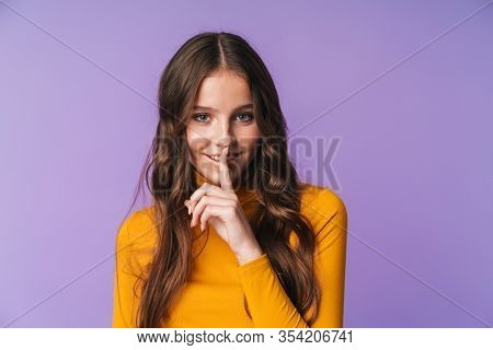 Image of young beautiful woman with long brown hair smiling and doing shh gesture isolated over violet background