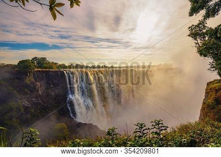 Sunset At The Victoria Falls On Zambezi River Located Between Zambia And Zimbabwe, The Largest Water
