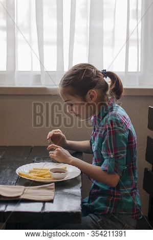 Girl Eating French-fries. Girl Eating French Fries In A Cafe. A Girl Of 9 Years Old Has Lunch With F
