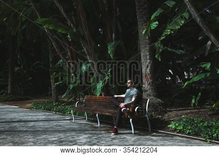 Relaxed young man sitting on the bench outdoors