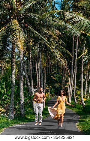 Beautiful Couple Running Among Palm Trees In Bali, Indonesia. Honeymoon On The Islands. A Happy Coup