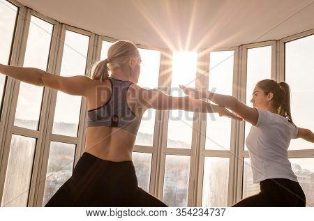 Two Beautiful Girls Practicing Yoga. Warrior Pose Virabhadrasana. Yoga Concept, Healthy Lifestyle
