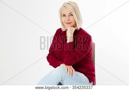 Close Up Portrait Of Smiling Blond Woman In Stylish Red Shirt Sitting On Chair On White Background