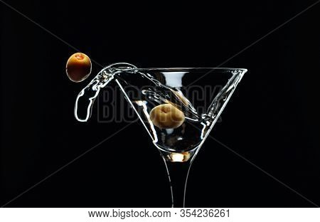 Martini Splash. Silhouette Of Martini With Green Olives On A Black Background.