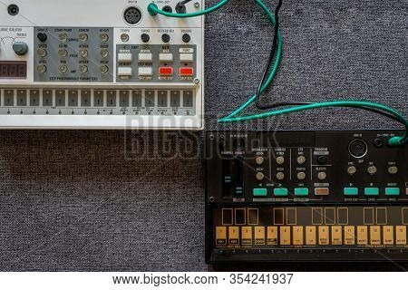 Top View Of Black Fm Synthesizer And A White Sampler Drum Box With Patch Cables With A Gray Textured
