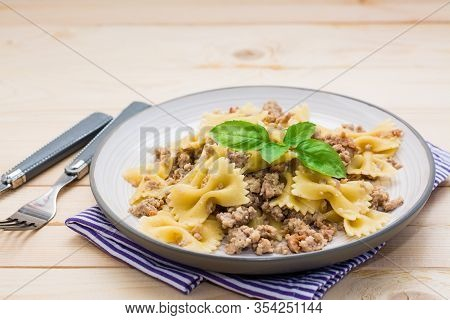 Ready-to-eat Pasta Navy With Minced Meat And Basil Leaves On A Plate On A Wooden Table. Russian Cuis