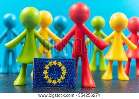 Crowd Of Multicolored Plastic Human Figures With Flag Of Europe Or European Flag. Concept Of Believe