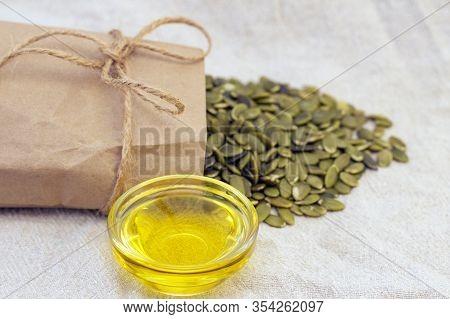 Pumpkin Seeds In A Paper Bag, Pumpkin Seed Oil On Natural Linen. Pumpkin Seeds Vitamins Of Group B A