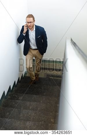 Image of handsome young businessman indoors walking by upstairs talking by mobile phone.
