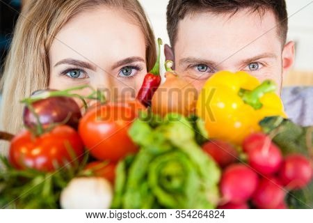 Smiling young couple hiding behind healthy fresh vegetables in the kitchen